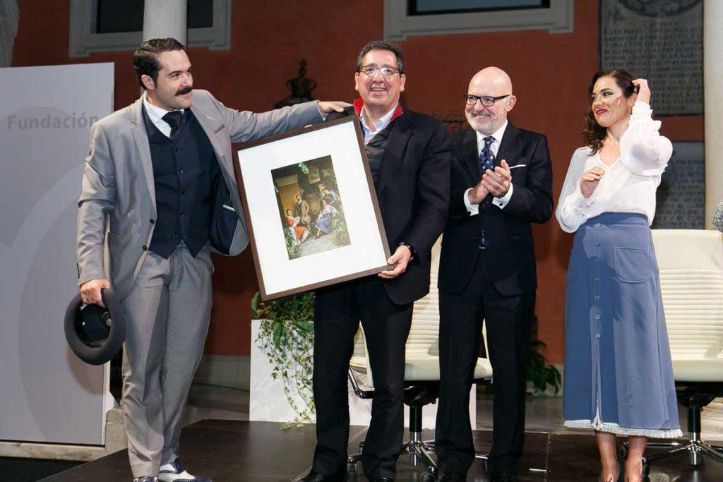 Antonio Pulido, presidente de la Fundación Cajasol, muestra el cuadro con el que le obsequiaron los actores de la IV edición de Letras en Sevilla